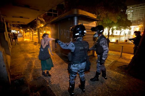 A military police pepper sprays a protester during a demonstration in Rio de Janeiro, Brazil, Monday, June 17, 2013. Protesters massed in at least seven Brazilian cities Monday for another round of demonstrations voicing disgruntlement about life in the country, raising questions about security during big events like the current Confederations Cup and a papal visit next month. (AP Photo/Victor R. Caivano)