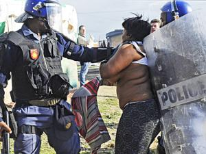A woman puts up a fight against two policemen, as rocks were thrown and rubber bullets fired during an eviction in Lwandle on Monday. Picture: Cindy Waxa